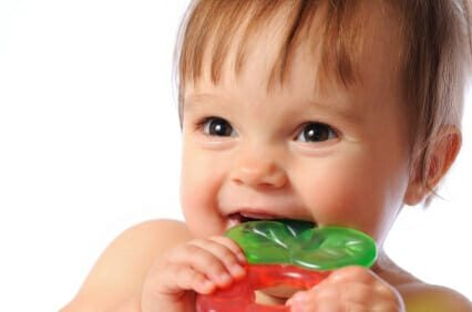 Toddler smiling and teething on a toy
